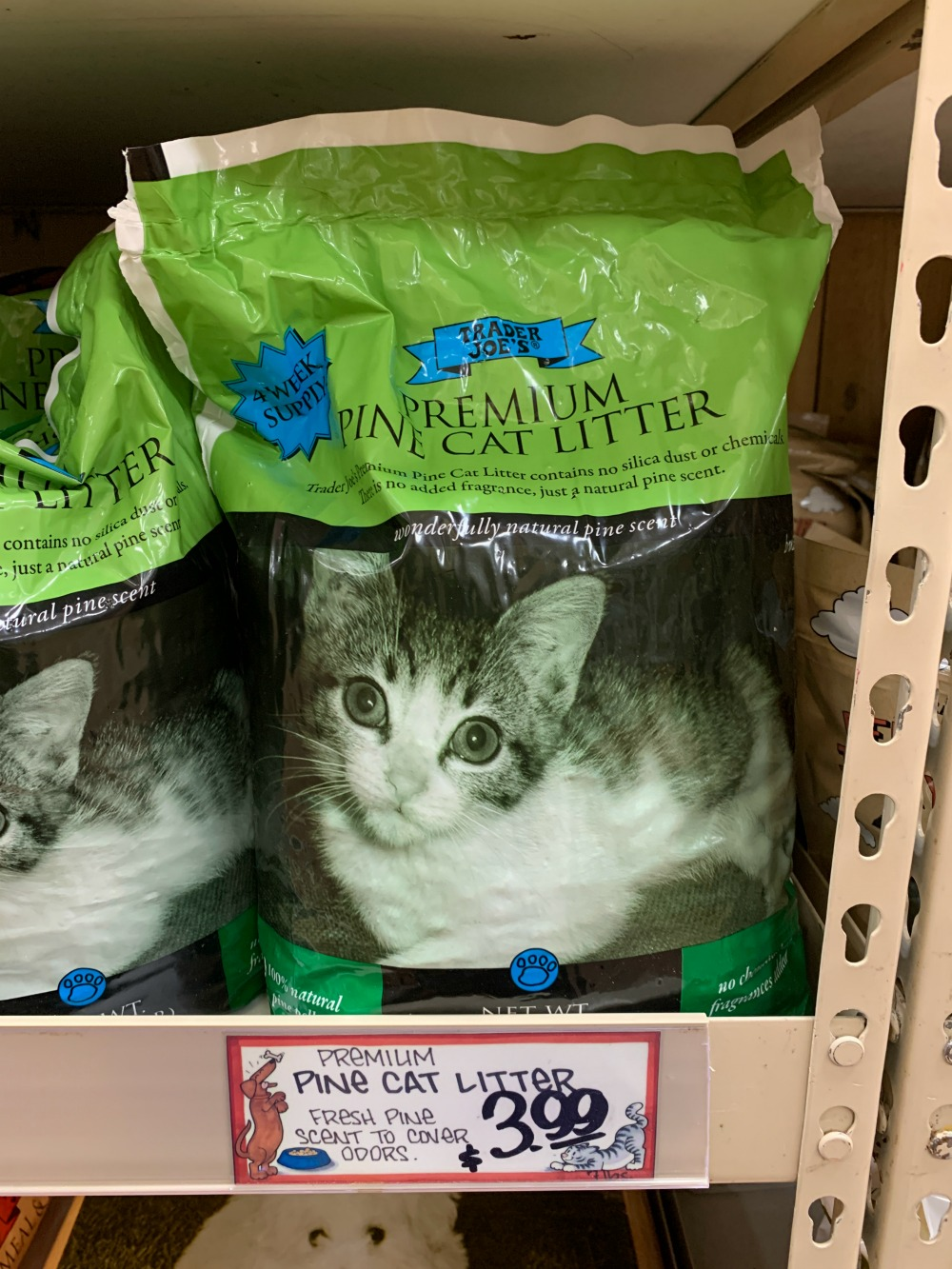 Trader Joe's premium pine cat litter bag sitting on a shelf in the store. Bag is green with a cat on the front.