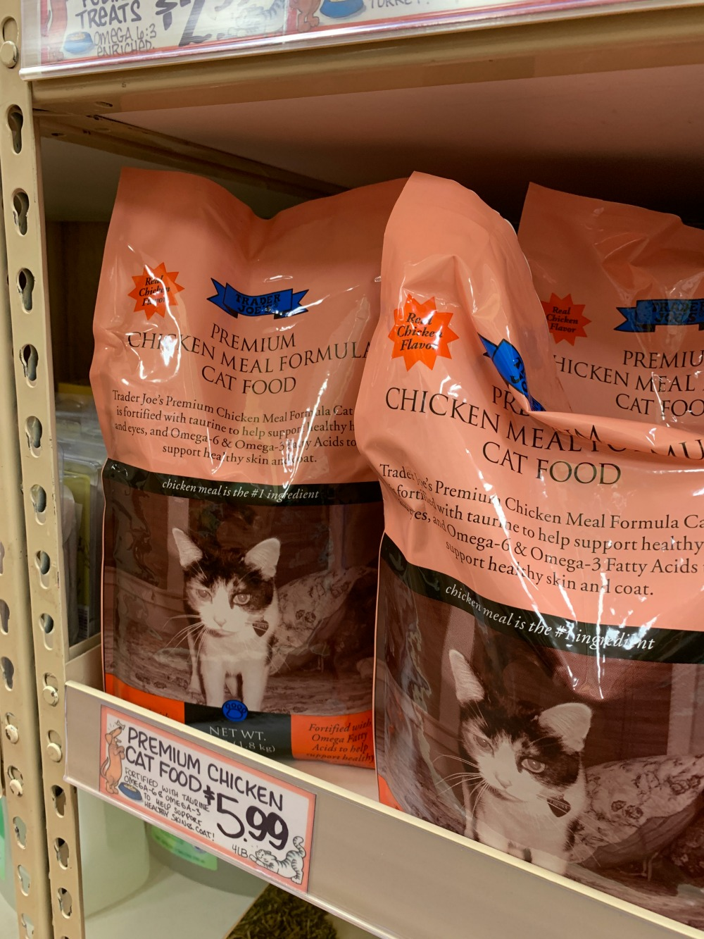 Bag of Premium Chicken Meal Formula Cat food from Trader Joe's. Bag is pink with a cat on the front.