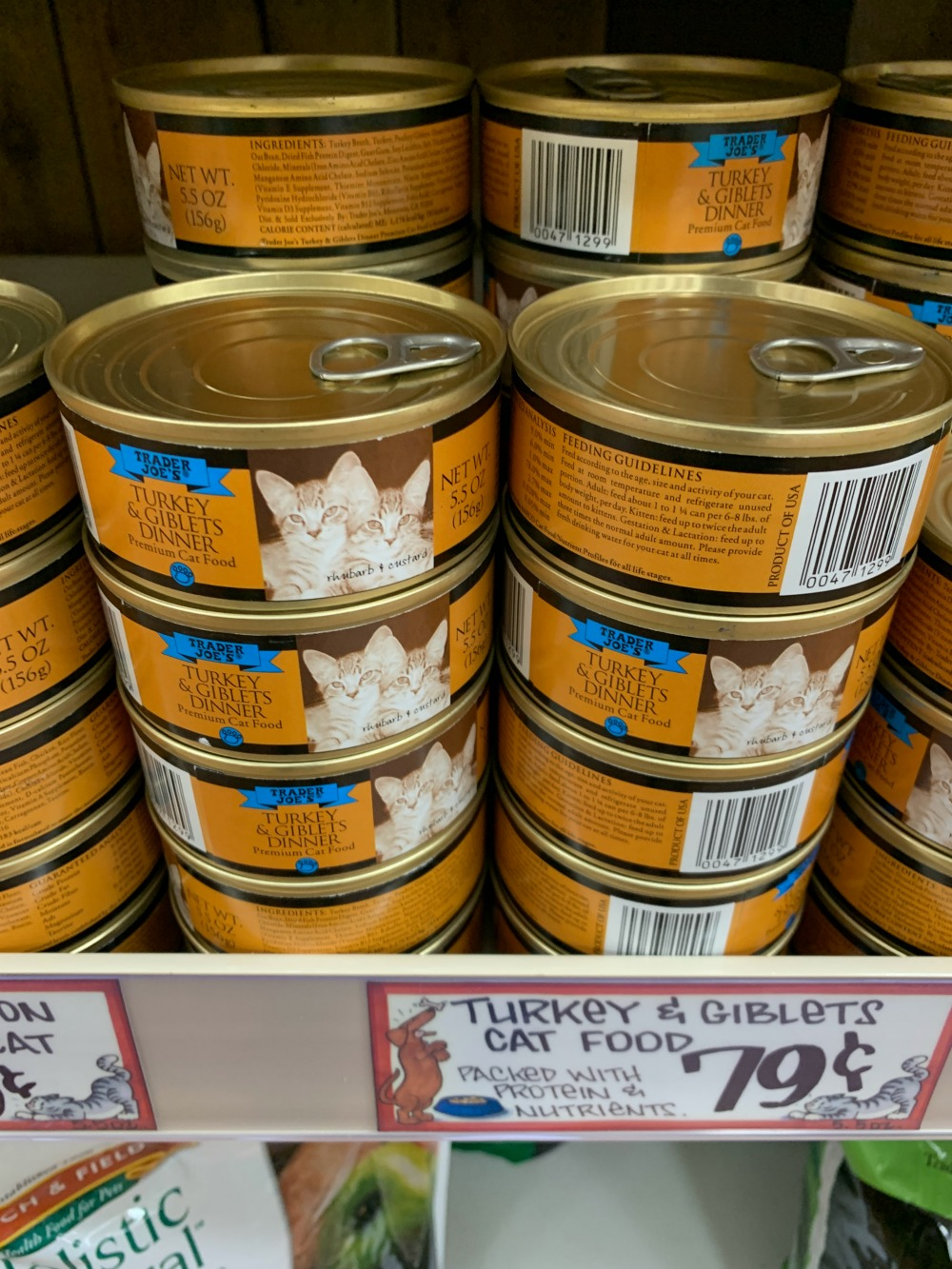 Stacked cans of Trader Joe's Turkey & Giblets wet cat food. Cans are orange with a picture of two cats on the front.